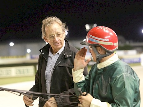 Ray Green gets the lowdown from stable driver Zachary Butcher after a race at Alexandra Park.