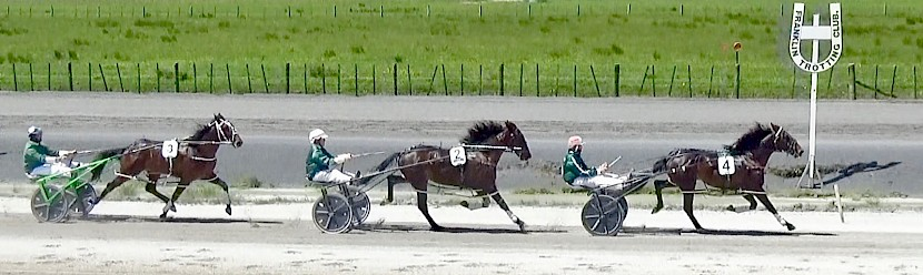 Perfect Stride leads Man Of Action and Sir Tiger with a lap to run in their mile qualifying heat at Pukekohe today.