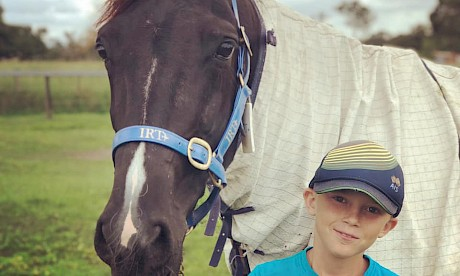 Trojan Banner pictured with his new best pal Chaise Saunders, nephew of trainer Al Barnes' partner Cassie.