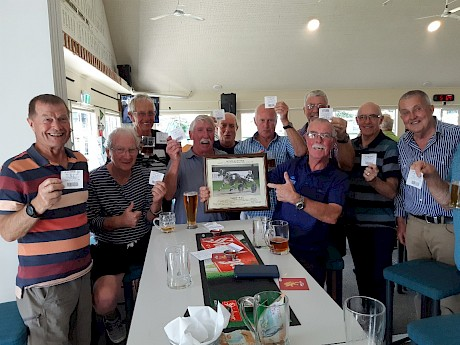 Co-owner Duncan Chisholm, holding a framed photo of Make Way, with his mates at Mangawhai last night, all holding winning tickets on the horse.