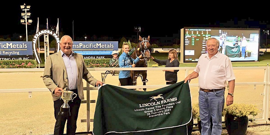 Lincoln Farms' boss John Street, right, and business manager Ian Middleton hold the winning rug for the Lincoln Farms Founders Cup won by Lincoln Farms' star Copy That. PHOTO: Megan Liefting/Race Images.